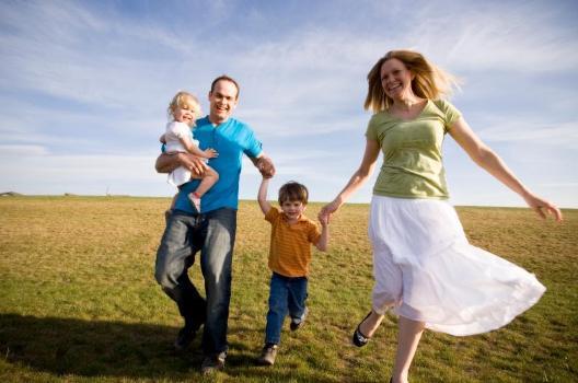 familia-de-mama-papa-hijo-e-hija-caminando-por-un-parque-felices